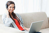 A smiling woman holding headphones and a laptop while looking at