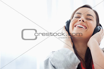 A laughing woman listening to her headphones