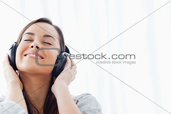 A smiling woman listening to her headphones