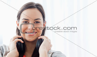 A smiling woman with headphones looks into the camera