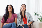 Two women sit beside on another on the couch while laughing 