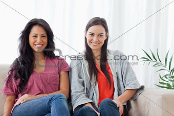 Two smiling women sit on the couch together while looking at the
