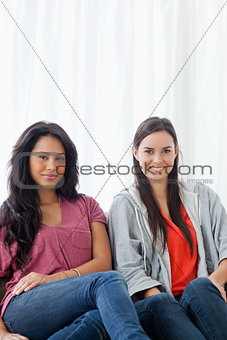 Half length shot of two women on the couch looking into the came