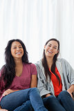 Two laughing women on the couch as they look straight ahead