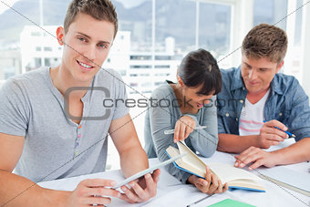 Three smiling students sitting and doing work as one looks at th