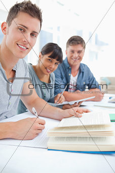 A close up of three studying friends as they look into the camer