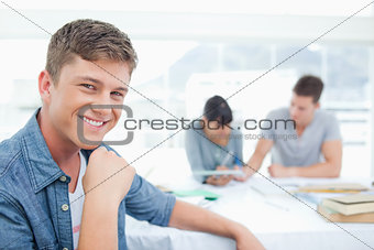 A smiling male sitting in front of his friends as he looks at th
