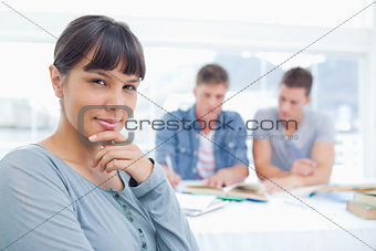 A woman looking at the camera thinking with her friends studying
