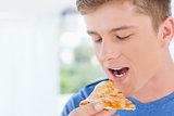 A man with a piece of pizza near his mouth