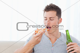 A man about to eat some pizza as he holds some beer