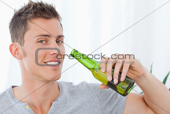 A smiling man with beer near to his mouth
