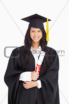 Woman with her degree dressed in her graduation gown