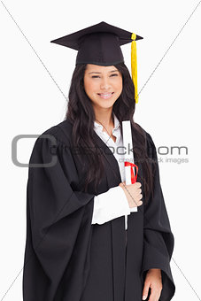 A smiling woman holding her degree as she has graduated from uni