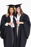 Two women embracing each other after they graduated from univers