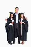 Full length of three friends graduate from college together