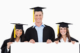 Three students having graduated holding a blank poster