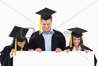 Three students having graduated holding blank sheet and looking