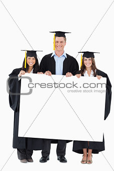 Full length of three graduates from college holding some blank p