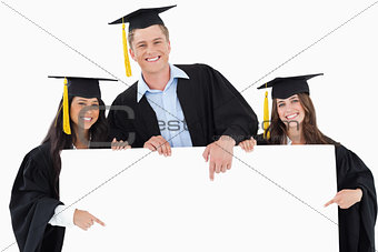 Three graduates pointing to the blank sign as they look at the c