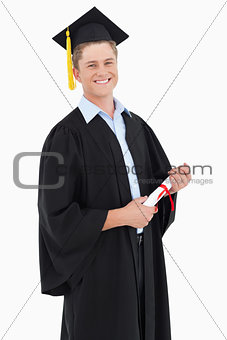 A smiling man looking at the camera as he graduates