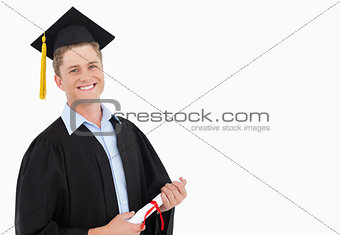 A smiling man with a degree in hand as he looks at the camera