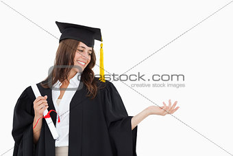 A woman holding her hand out with a degree in her other hand as