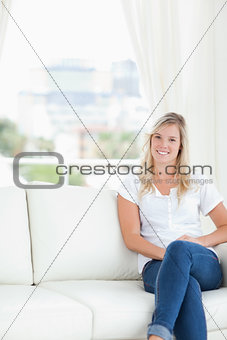 A smiling woman with her legs crossed