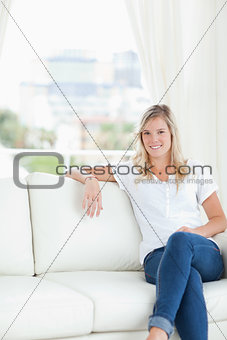 A woman with her arm resting on the couch as she sits and smiles