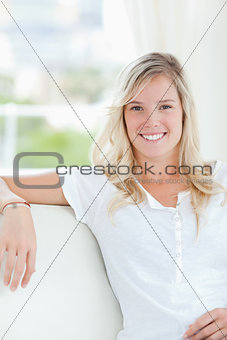 A smiling woman sitting on the couch as she looks into the camer
