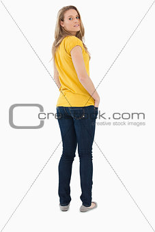 Back view of a young woman posing hands in the pockets