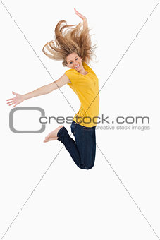 Blonde woman in yellow shirt jumping