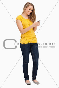 Attractive blonde woman smiling while using her cellphone