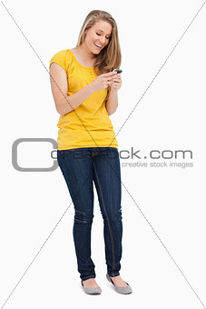 Attractive blonde woman laughing while using her cellphone