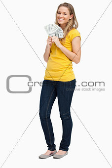 Blonde woman smiling while holding a lot of dollars