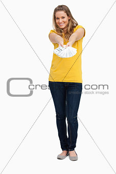 Attractive blonde woman smiling while holding a lot of dollars