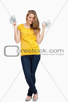 Beautiful blonde woman smiling with a lot of dollars