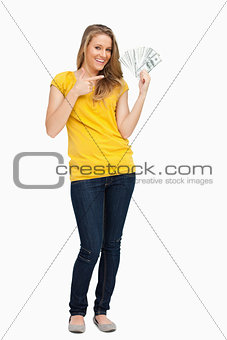 Beautiful blonde woman smiling while showing a lot of dollars
