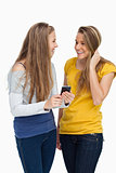 Two females student laughing while holding a cellphone