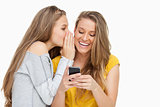 Young woman whispering to her friend who's texting on her phone