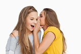 Young woman whispering to her friend