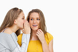 Blonde student whispering to her beautiful friend