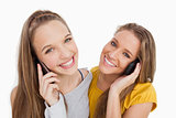 Close-up of two young women smiling on the phone