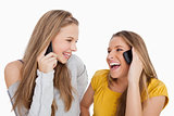 Close-up of two young women laughing on the phone