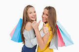 Rear view of two young women the thumb-up with shopping bags