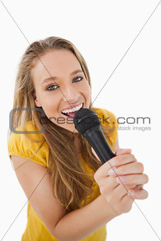 Close-up of a blonde singing with a microphone