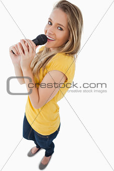 Fisheye view of a blonde girl singing with a microphone