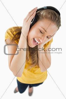 Fisheye view of a blonde girl enjoying music with headphones