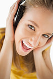 Close-up of a blonde girl enjoying music with headphones