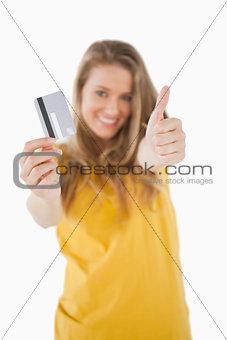 Portrait of a blonde student tending a credit card with the thum