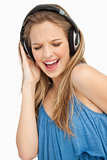 Close-up of a beautiful young woman singing while listening to m